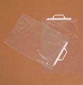 photo of two transparent carrier bags on a brown background